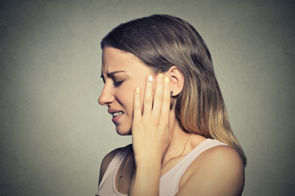 Closeup side profile sick young woman having ear pain touching her painful head isolated on blue background